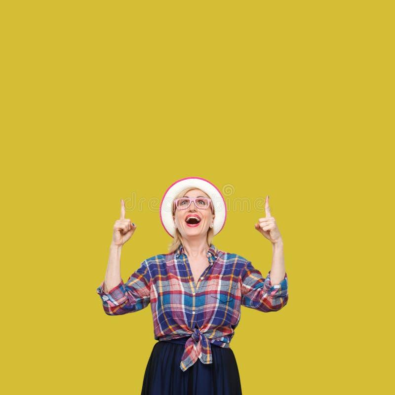 Portrait de femme mûre élégante moderne étonnée dans le style occasionnel avec la position de chapeau et de lunettes, regarder st image stock