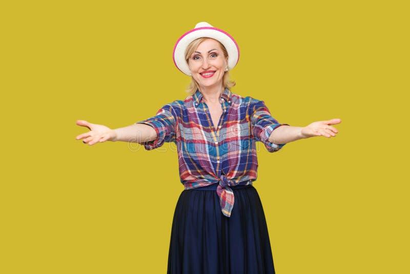 Portrait de femme mûre élégante moderne paisible heureuse dans le style occasionnel avec la position blanche de chapeau avec les  photo stock