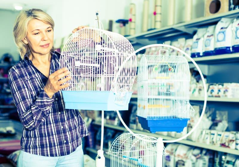 Portrait de femme mûre achetant la cage à oiseaux dans le petshop photographie stock libre de droits