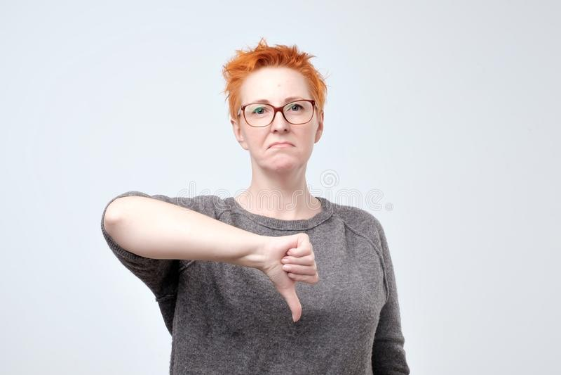 Portrait de femme mûre avec les verres de port de cheveux rouges montrant un signe d'aversion images libres de droits