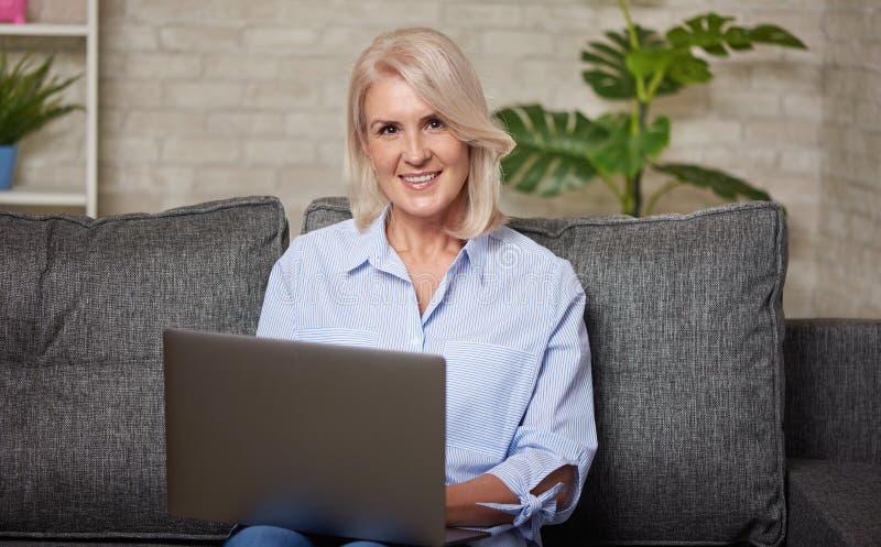Portrait de femme mûre de sourire avec l'ordinateur portable image stock
