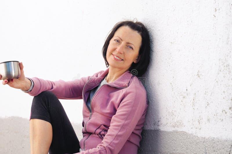 Portrait de femme mûre se reposant après essai près du mur avec la tasse à disposition photos libres de droits