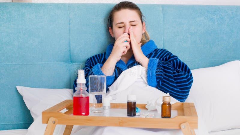 Portrait de femme malade avec la grippe se situant dans le lit et à l'aide de la pulvérisation nasale pour arrêter l'écoulement n images stock