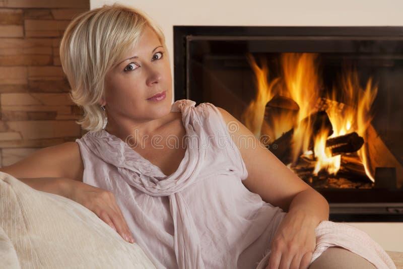 Portrait de femme par la cheminée à la maison photo libre de droits