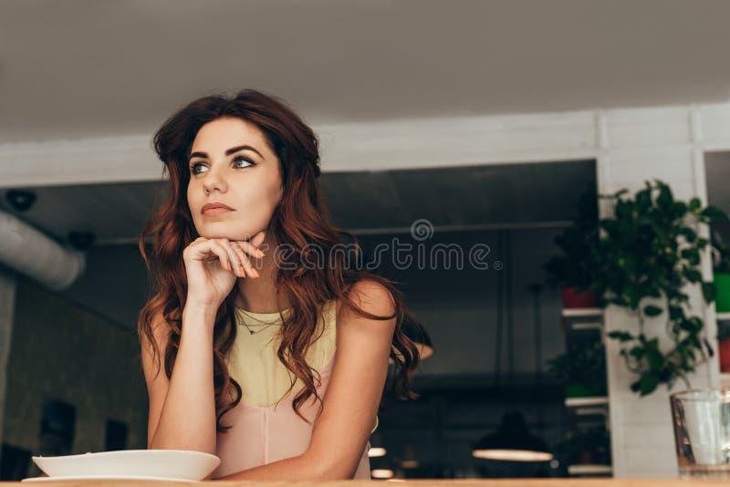 portrait de femme réfléchie se reposant à la table image stock