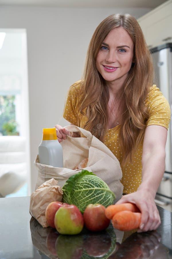 Portrait de femme retournant à la maison du voyage d'achats déballant les sacs d'épicerie libres en plastique photographie stock