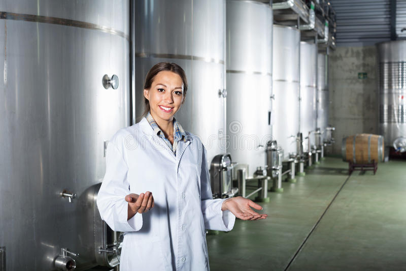 Portrait de femme se tenant sur l'usine de vin dans la section secondaire de fermentation photo stock