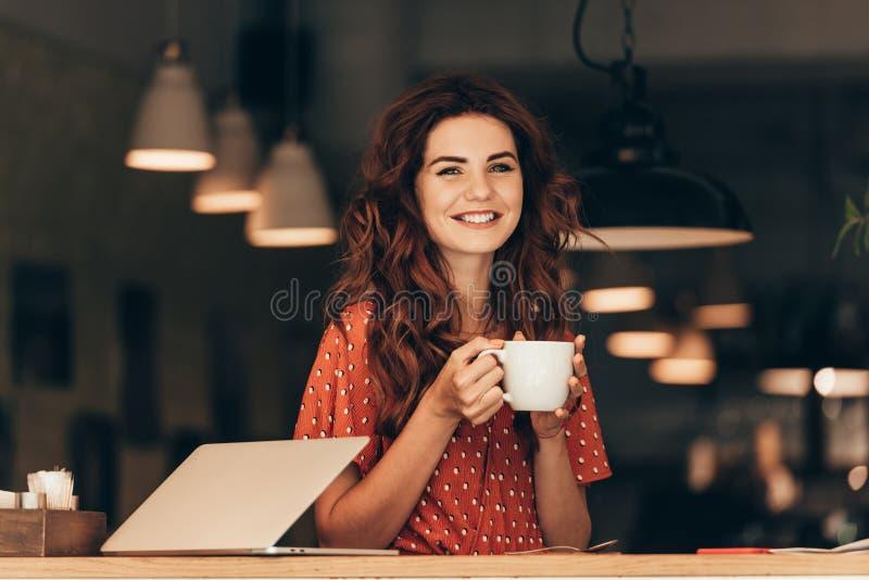 portrait de femme de sourire avec la tasse de café à la table avec l'ordinateur portable image libre de droits
