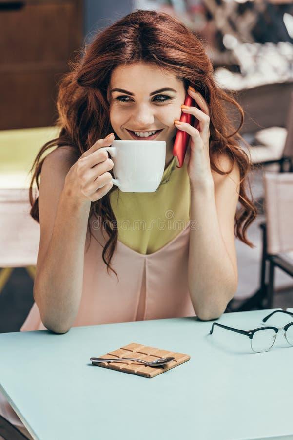 portrait de femme de sourire avec la tasse de café parlant sur le smartphone image stock