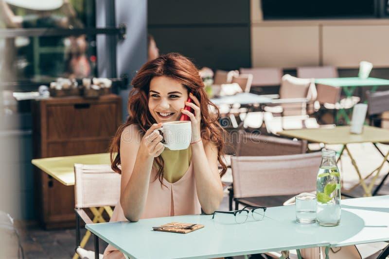 portrait de femme de sourire avec la tasse de café parlant sur le smartphone photos libres de droits