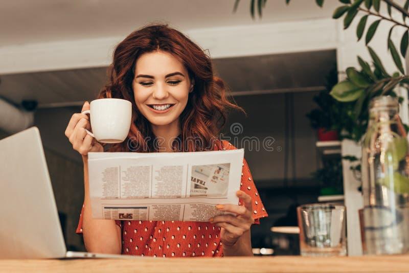portrait de femme de sourire avec la tasse du journal de lecture de café à la table avec l'ordinateur portable images libres de droits