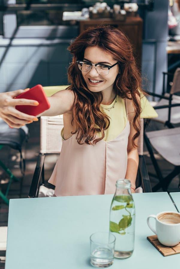 portrait de femme de sourire dans des lunettes prenant le selfie sur le smartphone photo stock