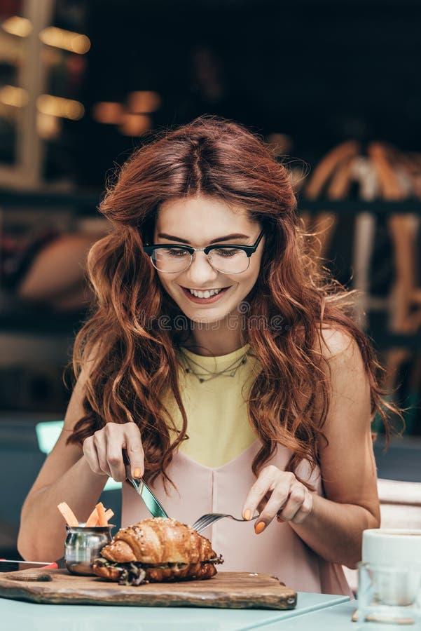 portrait de femme de sourire dans des lunettes prenant seul le petit déjeuner photographie stock