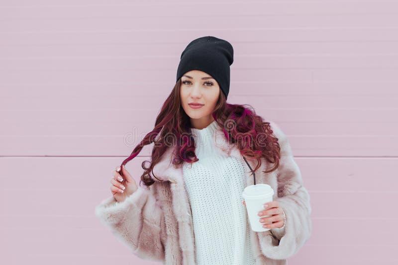 Portrait de femme de sourire de mode de beauté avec du café dans le manteau de vison et le chapeau noir sur le fond rose le Copie photographie stock libre de droits