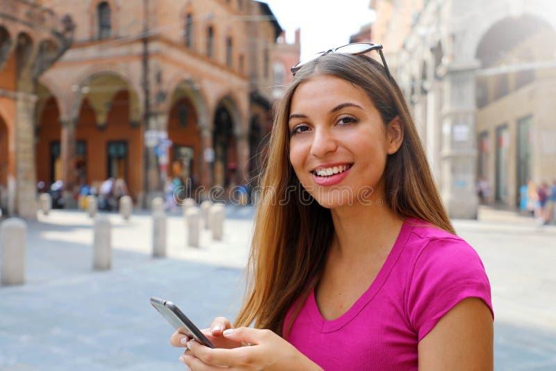 Portrait de femme de sourire regardant la caméra et à l'aide du téléphone intelligent dans la vieille ville médiévale photos stock