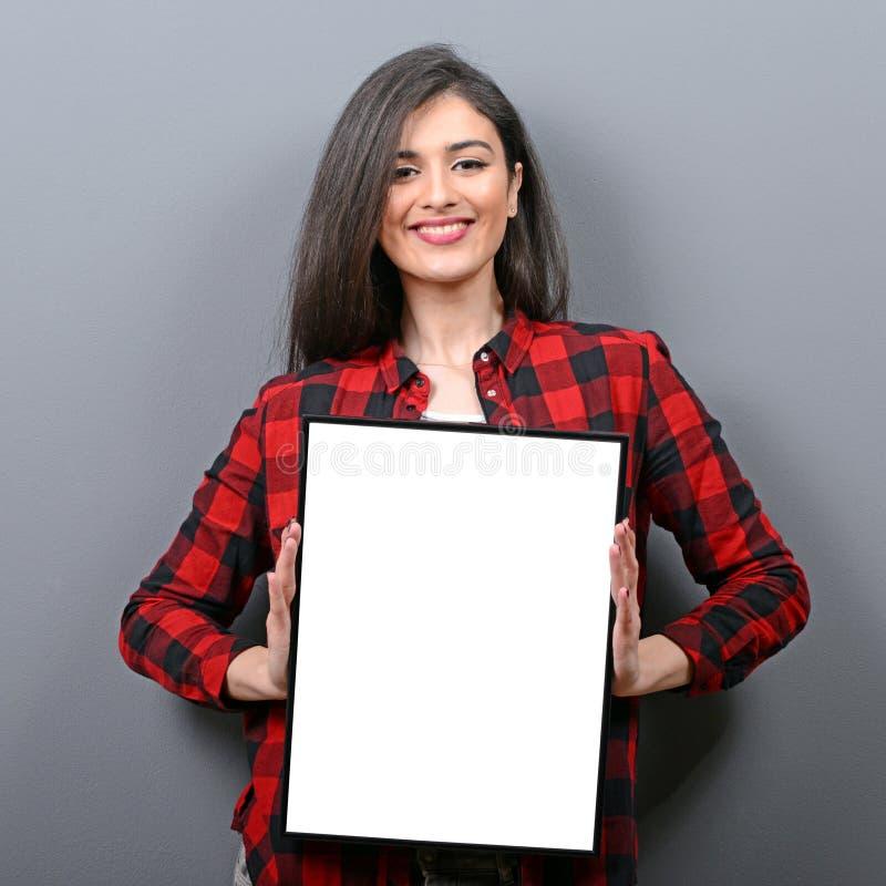 Portrait de femme de sourire tenant le panneau vide de signe Portrait de studio de jeune femme avec la carte de signe sur le fond photo stock