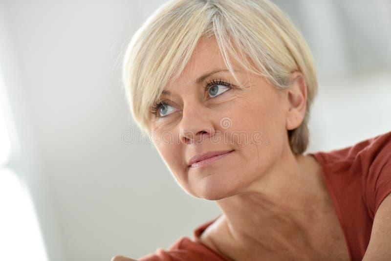 Portrait de femme supérieure blonde à la maison image libre de droits