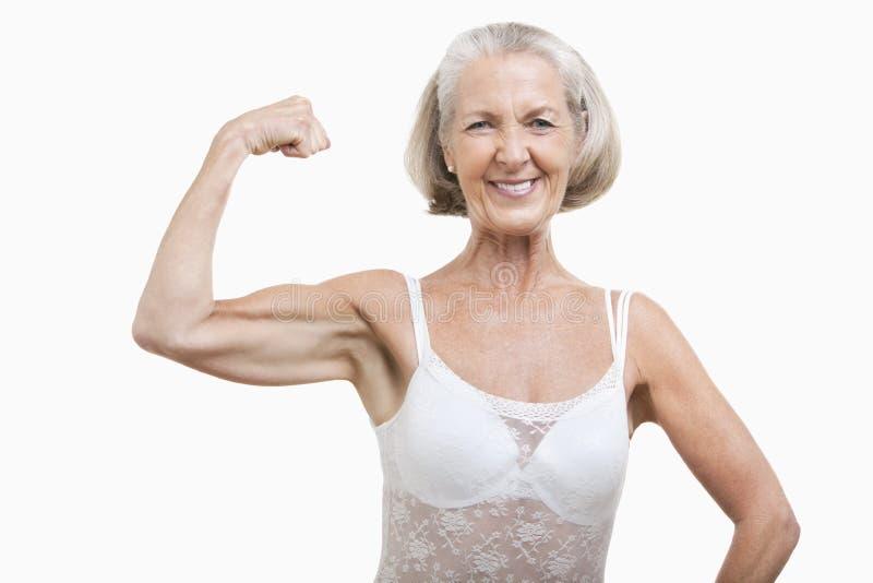 Portrait de femme supérieure fléchissant des muscles sur le fond blanc images stock