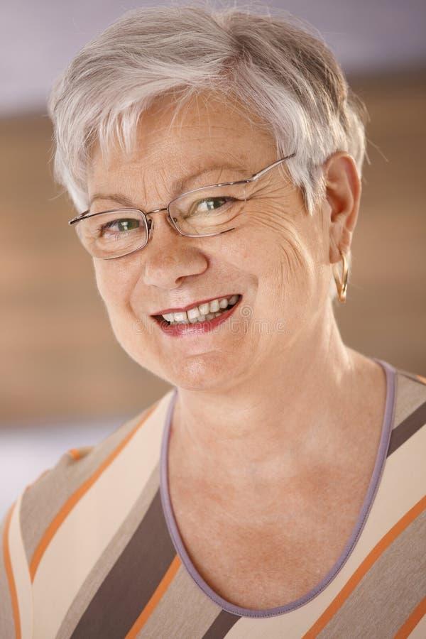 Portrait de femme supérieure heureuse avec des verres photo stock