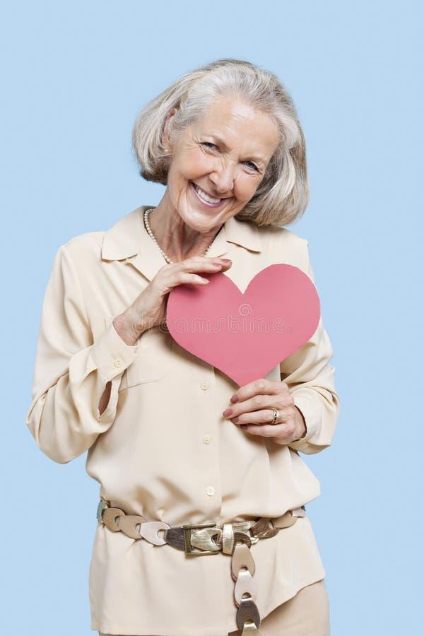 Portrait de femme supérieure tenant le coeur de papier rouge sur le fond bleu photos libres de droits