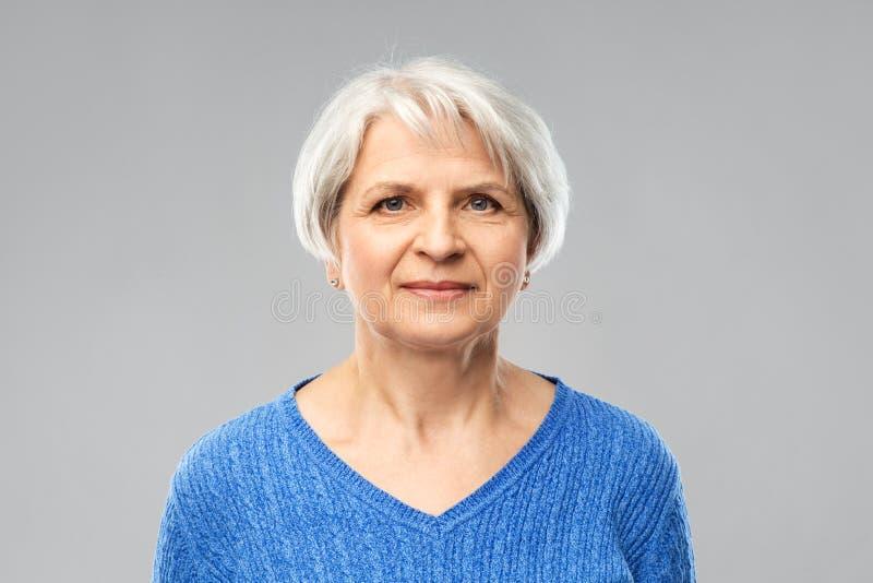 Portrait de femme sup?rieure dans le chandail bleu au-dessus du gris photos stock
