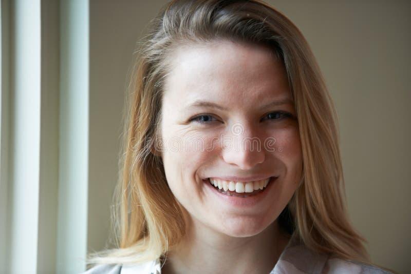 Portrait de fenêtre se tenante prêt de sourire de jeune femme photographie stock libre de droits