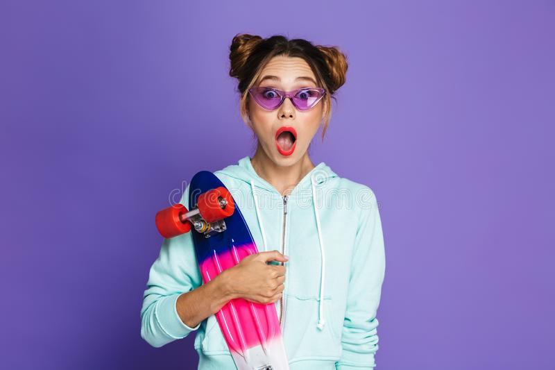 Portrait de fille adolescente de patineur avec deux petits pains dans le smil de lunettes de soleil images stock