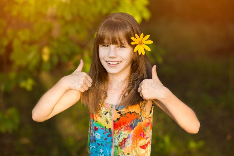 Portrait de fille adorable avec la fleur dans des poils, montrant des pouces  image stock