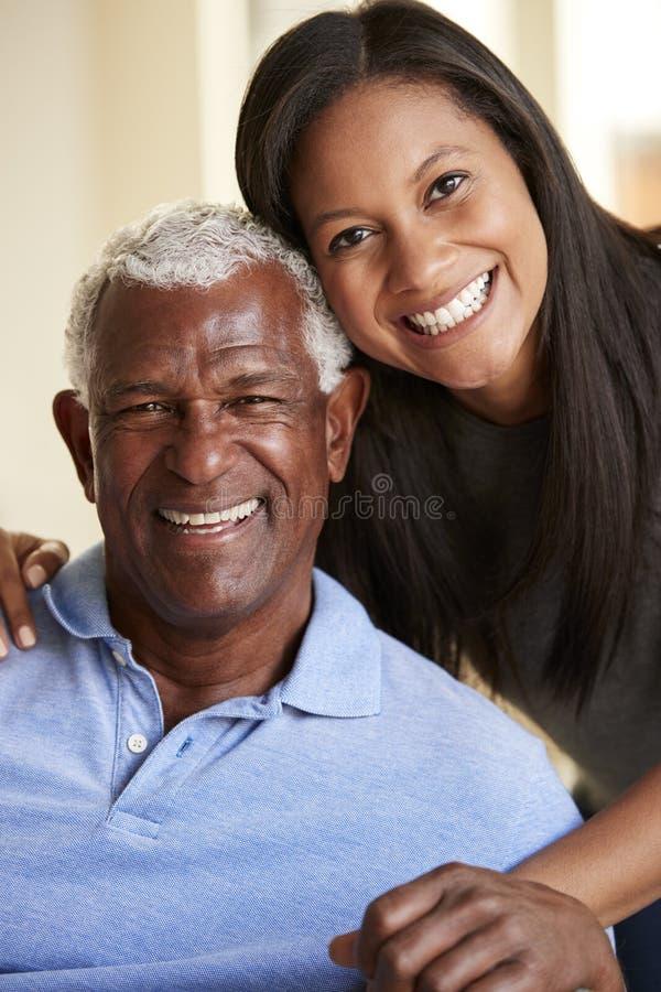 Portrait de fille adulte de sourire de Being Hugged By de père supérieur à la maison photographie stock libre de droits