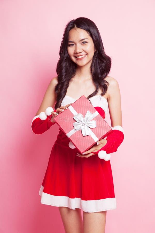 Portrait de fille asiatique mignonne de Santa Claus de Noël avec le cadeau rouge photographie stock libre de droits