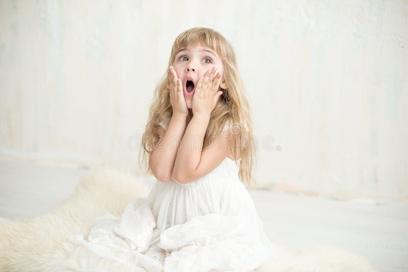 Portrait de fille assez petite dans la robe blanche, elle est étonnée et a mis ses mains sur des joues photos stock