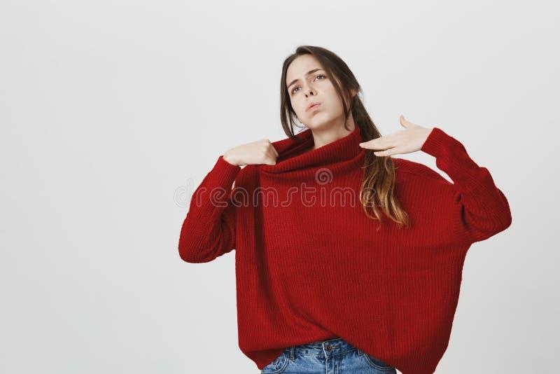 Portrait de fille attirante élégante, faire des gestes, se sentant chaud dans le chandail rouge d'hiver au-dessus du fond blanc L photographie stock