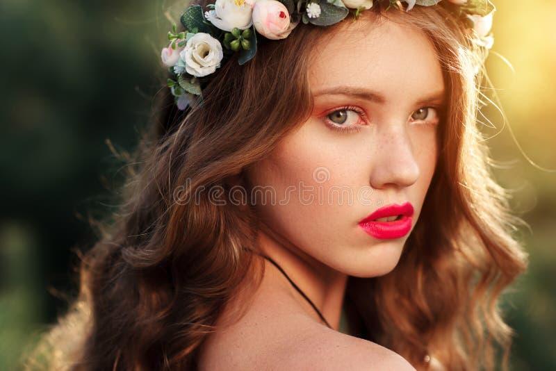 Portrait de fille attirante en guirlande au coucher du soleil image stock
