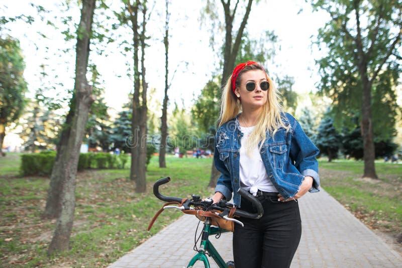 Portrait de fille attirante en parc avec la bicyclette tout en marchant La jeune femme avec un vélo se tient en parc photographie stock
