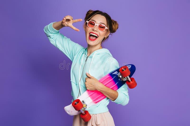 Portrait de fille attirante de patineur avec deux petits pains dans des lunettes de soleil h photos stock