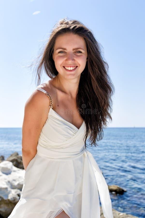 Portrait de fille aux cheveux longs drôle dans la robe de mariage contre le bord de la mer photos stock