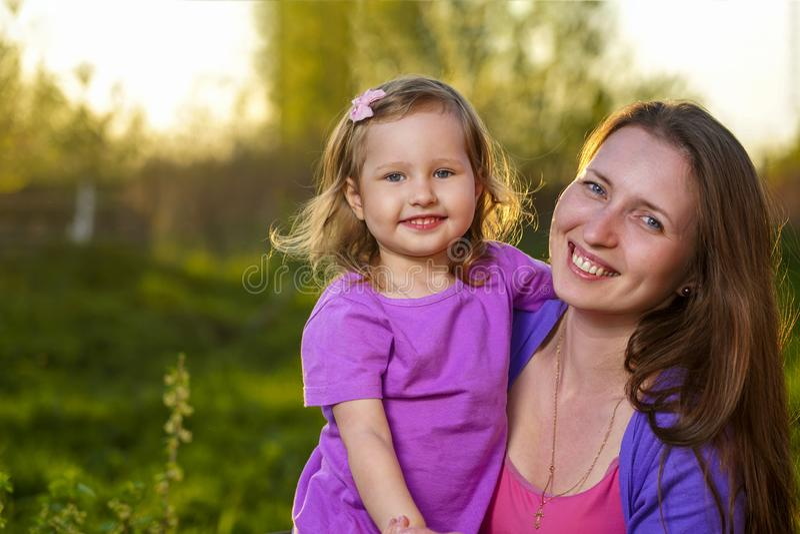 Portrait de fille blonde attirante et sa de mère embrassant regardant la caméra et souriant dehors images stock