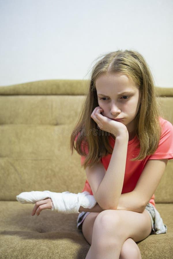 Portrait de fille blonde caucasienne avec la main blessée en plâtre photo stock