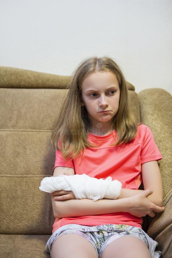 Portrait de fille blonde caucasienne déprimée avec la main blessée en plâtre image stock