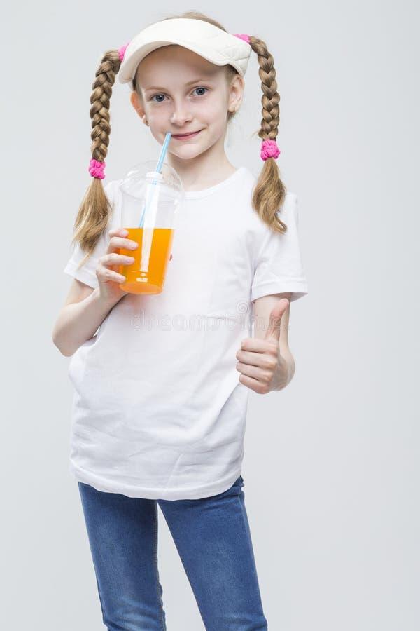 Portrait de fille blonde caucasienne de sourire heureuse dans le pare-soleil tenant la tasse de Juce photo stock