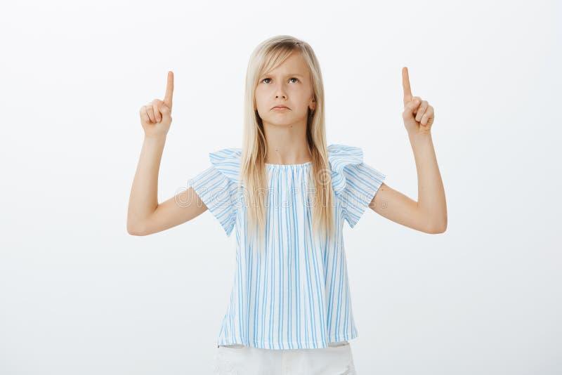 Portrait de fille blonde mignonne offensée déçue dans le chemisier bleu, regardant et se dirigeant avec des index, fronçant les s photographie stock