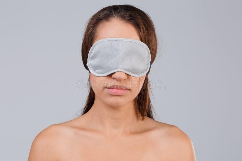 Portrait de fille de brune dans le masque pour le sommeil sur un fond gris images libres de droits
