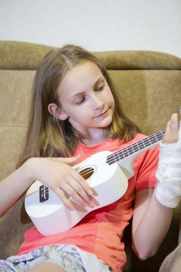 Portrait de fille caucasienne avec la main blessée en plâtre jouant la guitare hawaïenne à l'intérieur photographie stock