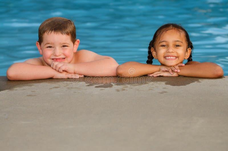 Portrait de fille caucasienne de garçon et de métis dans la piscine photo stock