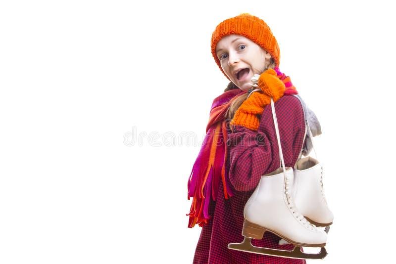 Portrait de fille caucasienne de hurlement dans des vêtements d'hiver posant avec des patins de glace des deux mains sur le fond  images stock