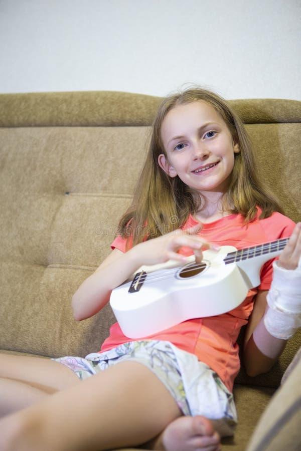 Portrait de fille caucasienne positive avec la main blessée en plâtre jouant la guitare hawaïenne à l'intérieur photographie stock libre de droits