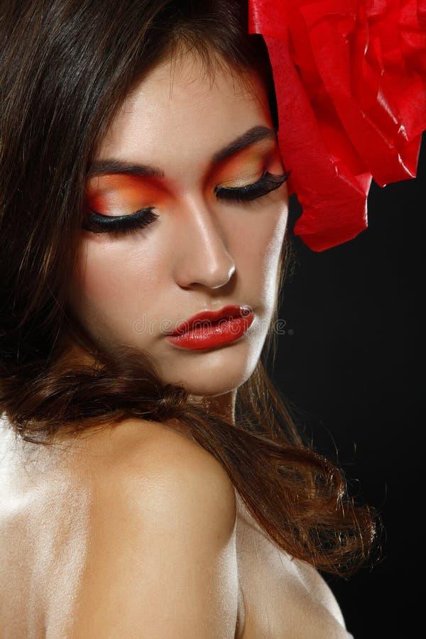 Portrait de fille de charme de mode avec la fleur rouge dans ses cheveux photos libres de droits