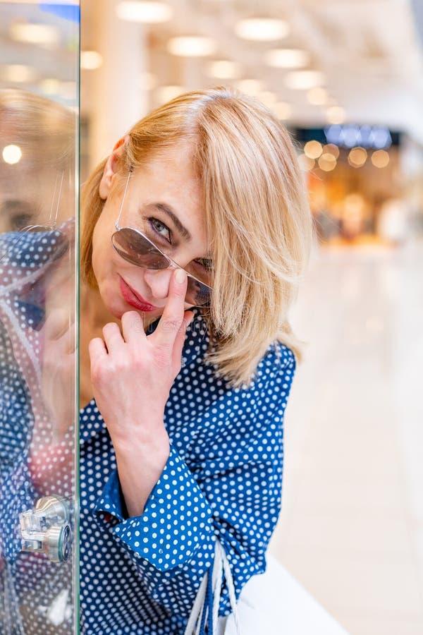 Portrait de fille d'achats de mode Femme de beauté souriant et regardant au-dessus des verres dans le centre commercial Client ve photo libre de droits