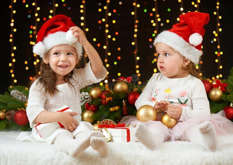 Portrait de fille d'enfant en décoration de Noël, émotions heureuses, concept de vacances d'hiver, fond foncé avec l'illumination photographie stock