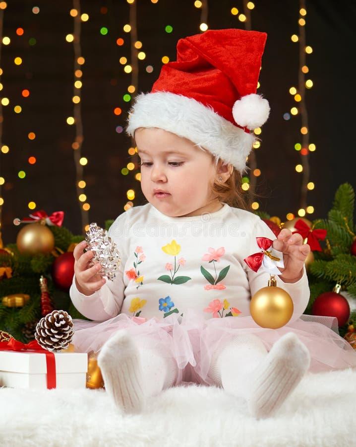 Portrait de fille d'enfant en décoration de Noël, émotions heureuses, concept de vacances d'hiver, fond foncé avec l'illumination photographie stock libre de droits